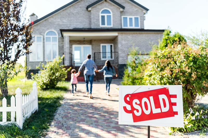 "Home ""for sale"" sign under a ""sold"" sign and a family in the background going into the new house"